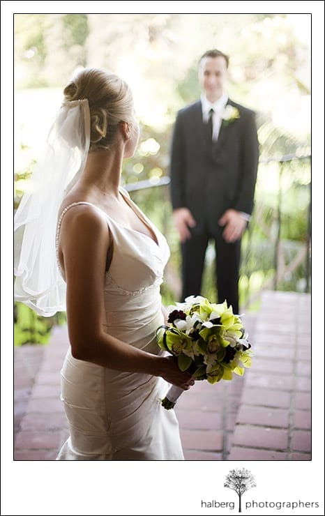 Jennifer looking at John while holding her wedding flowers at the Santa Barbara Courthouse