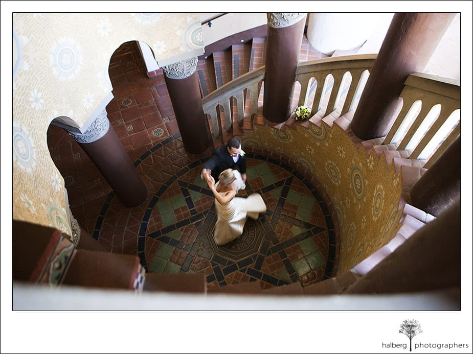 John and Jennifer dance at bottom of stairwell at their santa barbara courthouse wedding