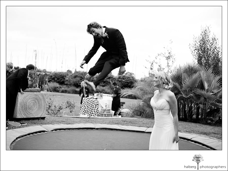 Groom jumping on trampoline with bride watching