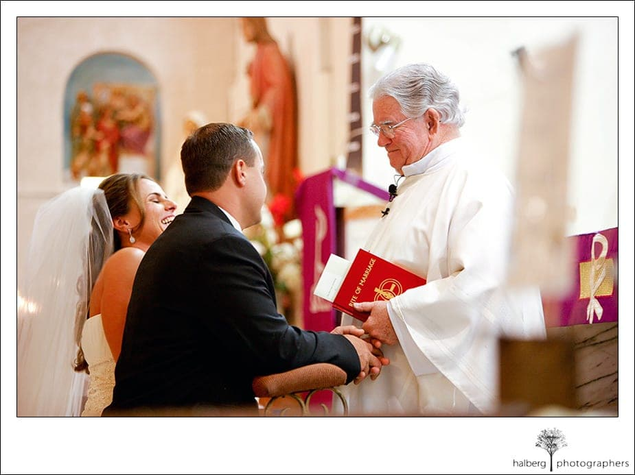 bride and groom with priest at alter of Our Lady of Solitude Parish