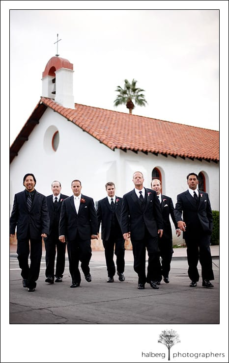 groom walking with groomsmen in front of Our Lady of Solitude Parish