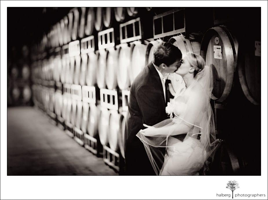 bride and groom kissing in barrel room chateau julien wine estate
