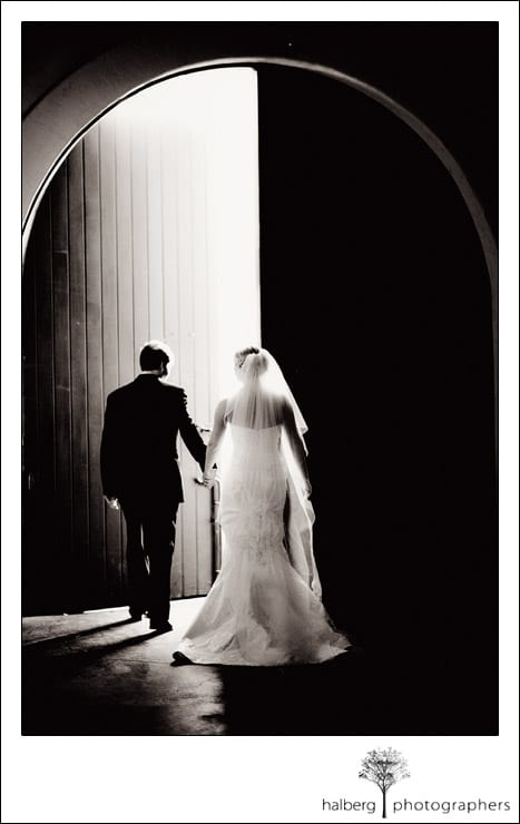bride and groom walking out of barrel room at chateau julien wine estate