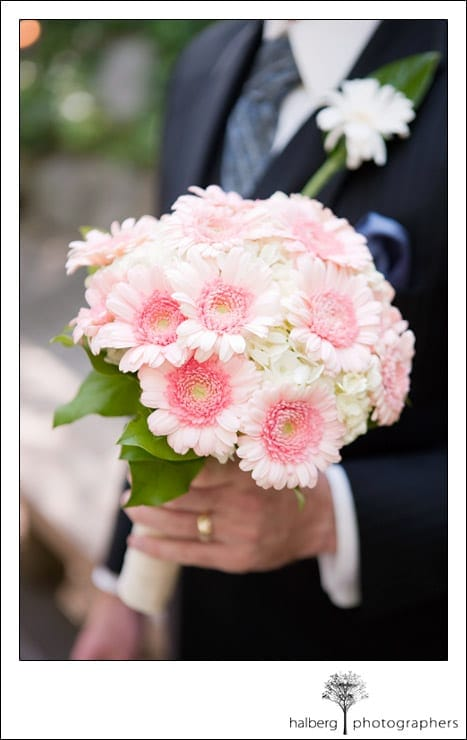 groom holding brides bouquet of pink and white gerber daisies