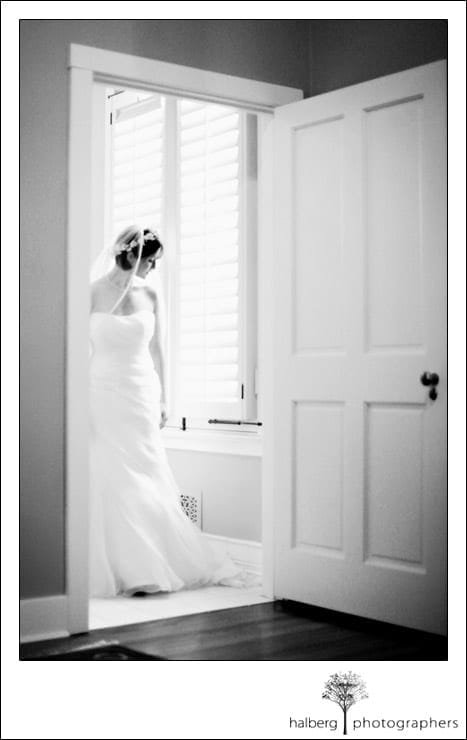 bride looking out window in private estate bathroom