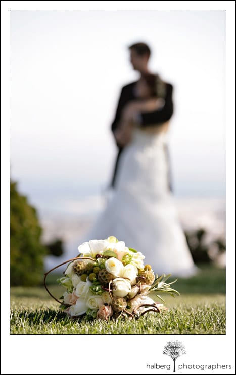 bridal bouquet in front of bride and groom embracing