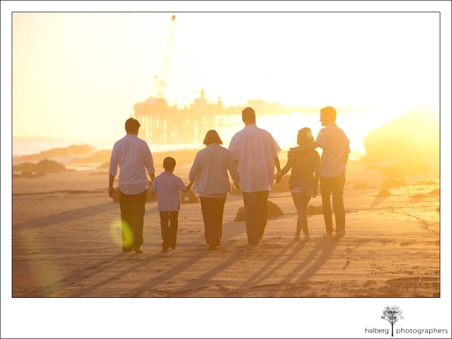 family walking along santa barbara beach during sunset