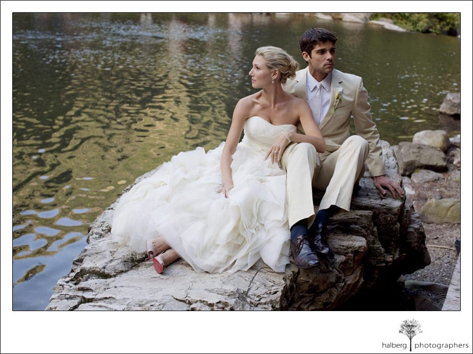 bride and groom sitting on rocks in front of pond at sundance wedding