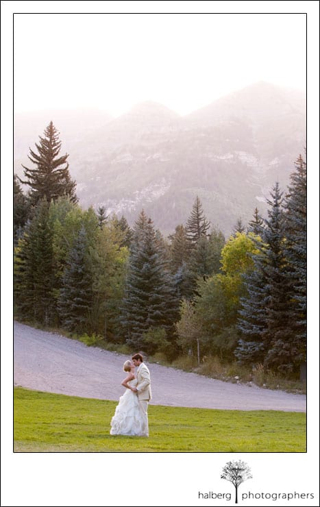 bride and groom kissing in field at sundance wedding