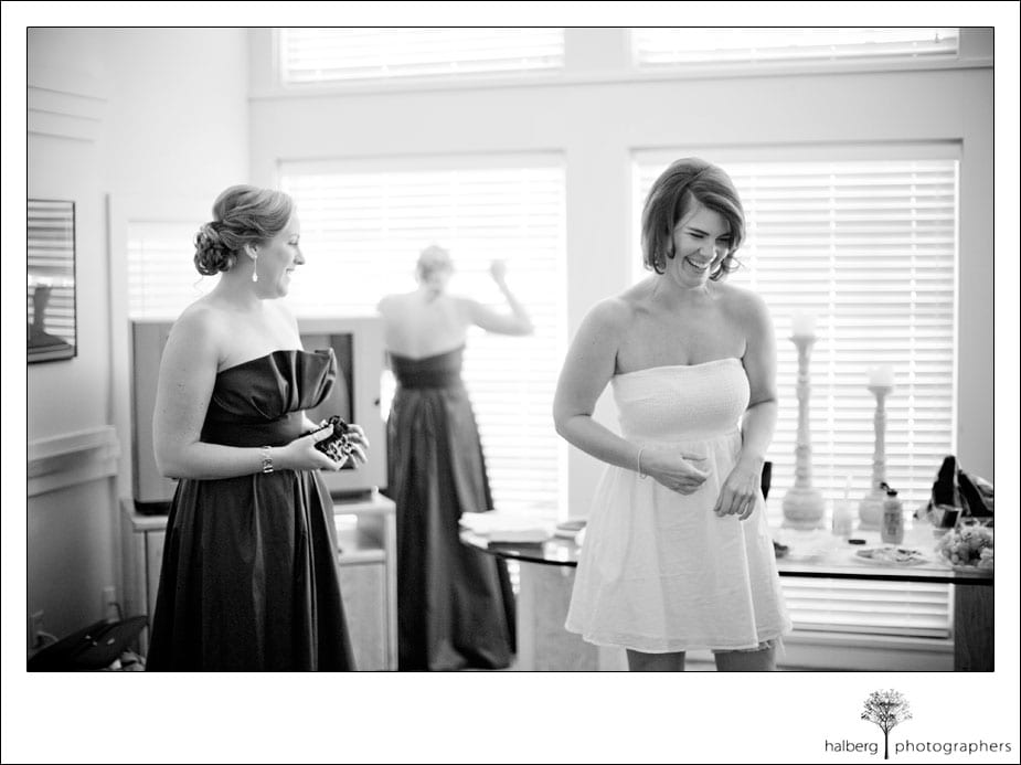 bride laughing with bridesmaids while getting ready for her wedding