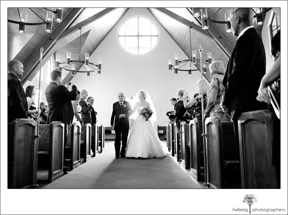 bride and father walking down isle of church
