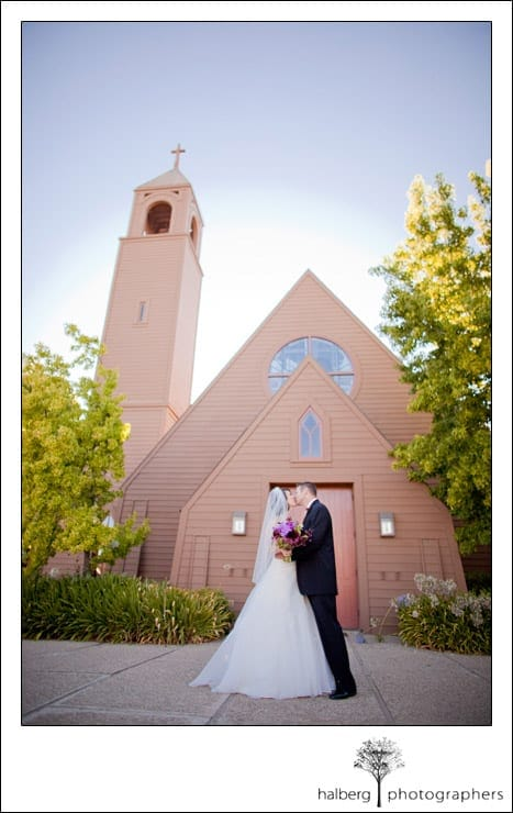 brideand groom kissing in front of church