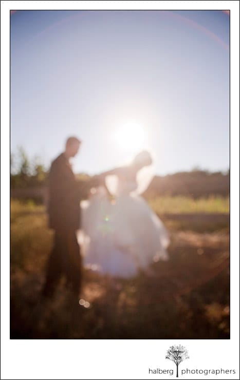 bride and groom walking through field out of focus