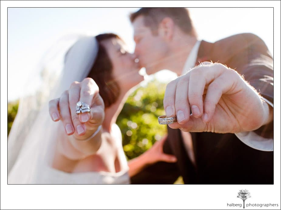 bride and groom holding out wedding rings while kissing