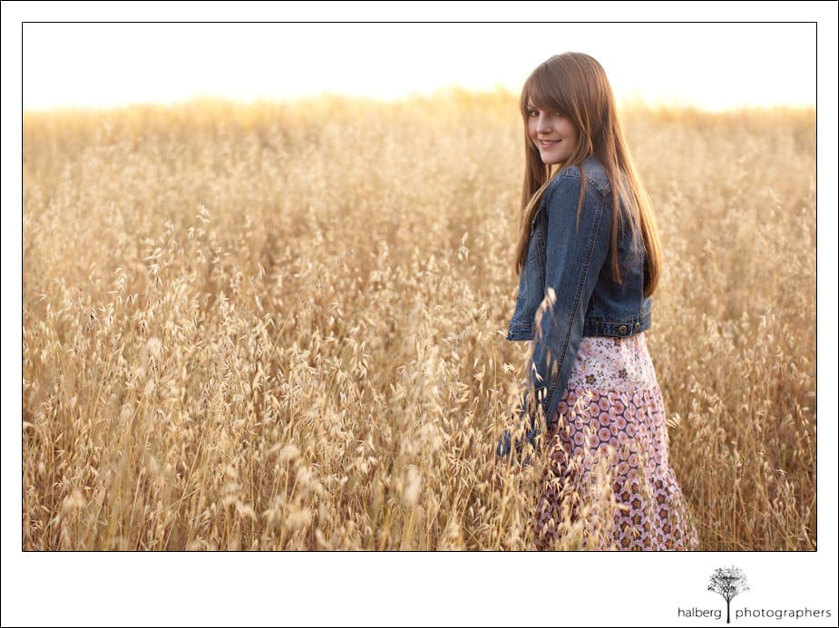 UCSB Senior walking away in field of tall grass
