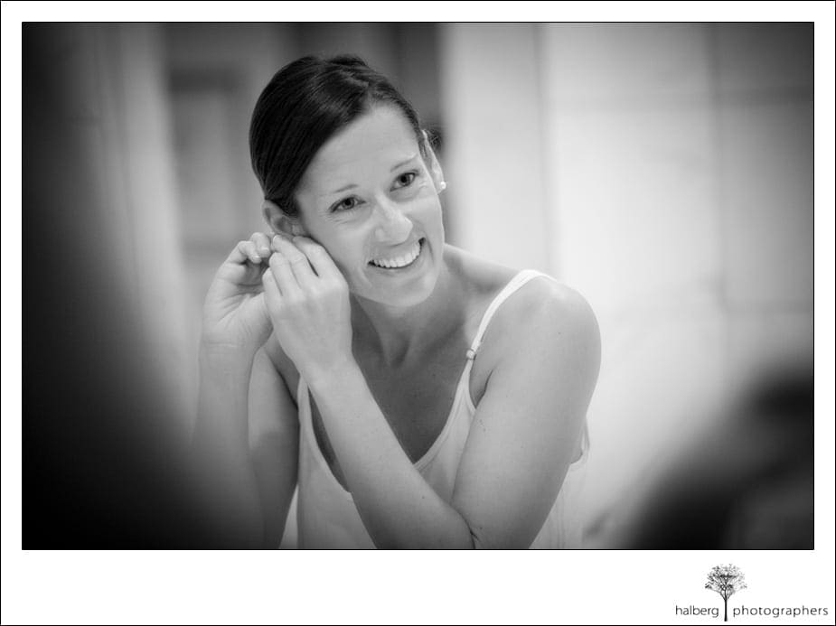 bride putting earings on for her shoestring winerey wedding