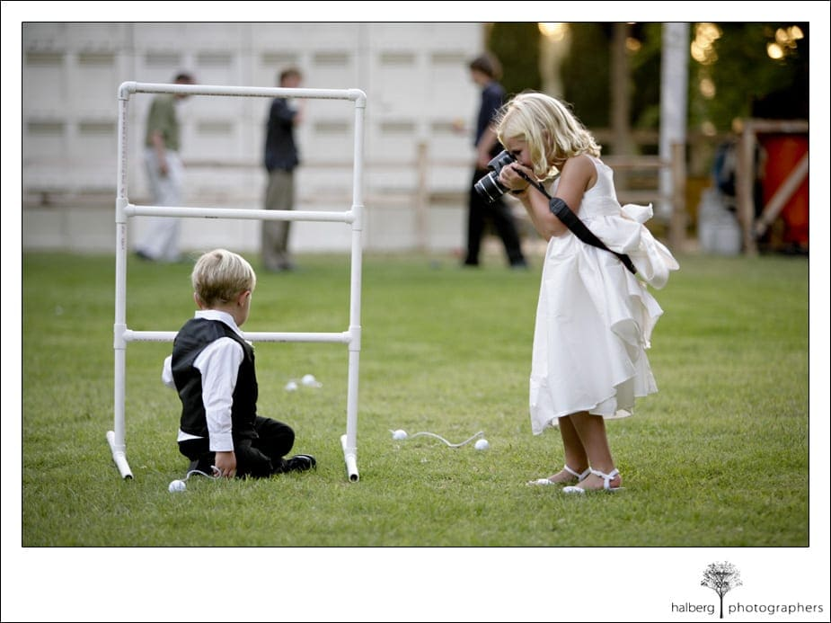 flower girl taking picture of ring bearer