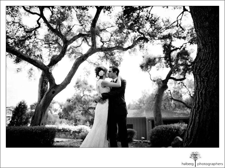 bride and groom embacing under oak trees at montecito wedding