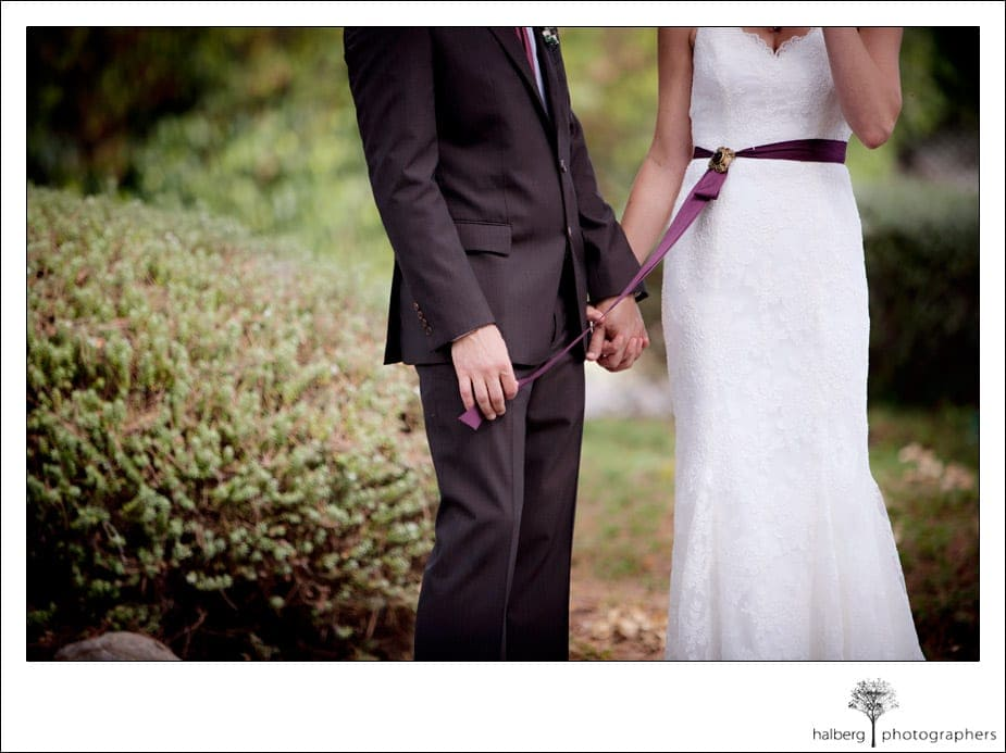 groom playing with bride's purple sash at montecito wedding