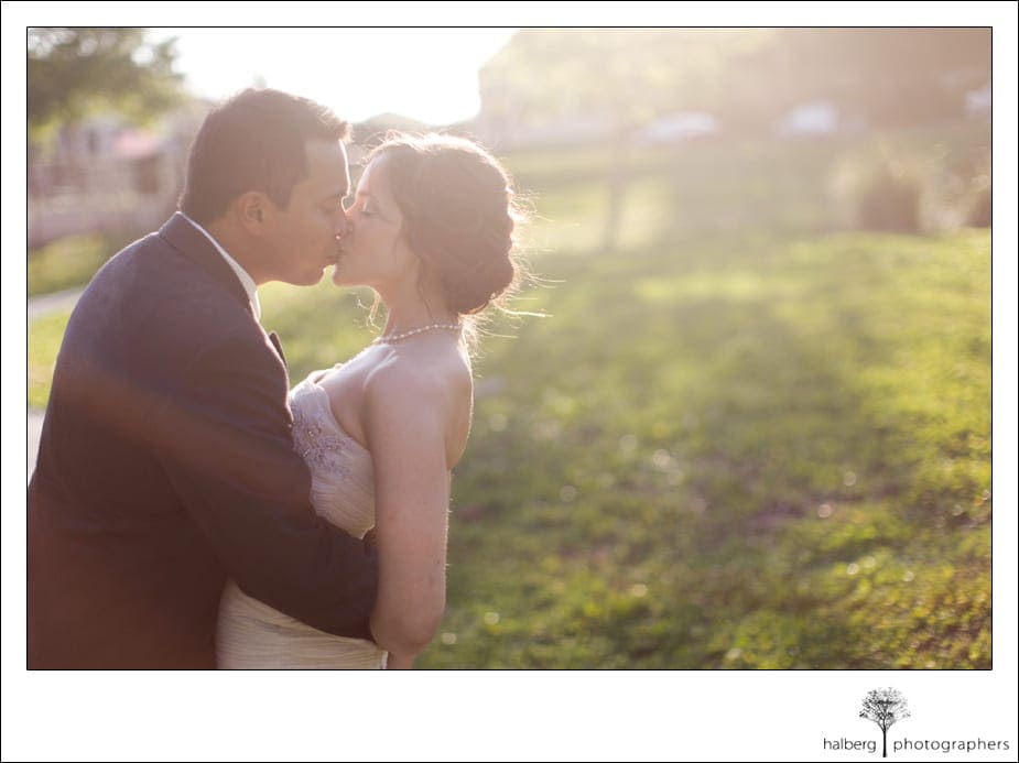 bride and groom kiss in field at their destination wedding