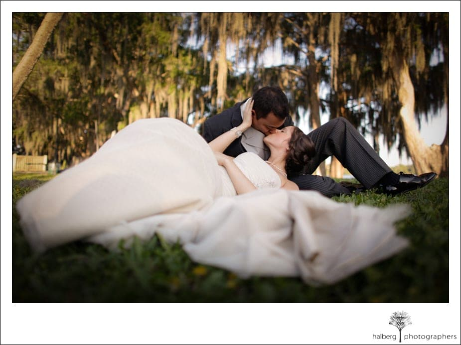 bride and groom laying on grass kissing after their destination wedding