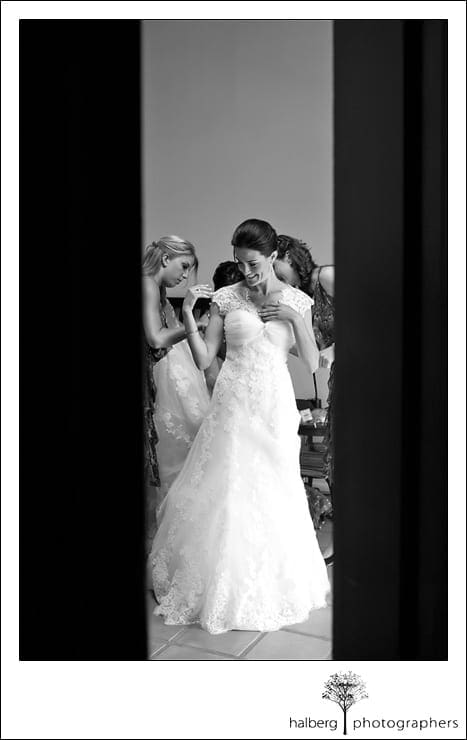 bride with bridesmaids putting dress on before her heartstone ranch wedding