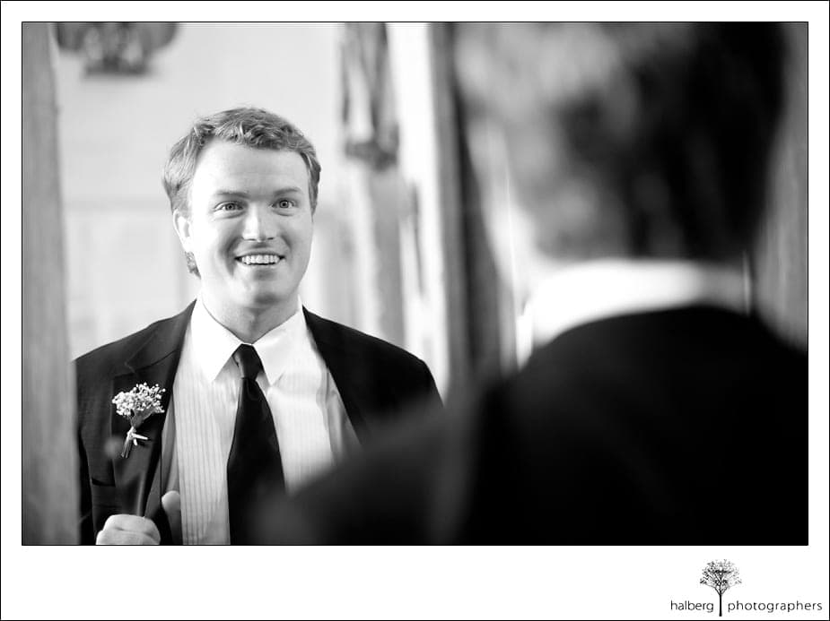 groom smiling looking in mirror before his heartstone ranch wedding