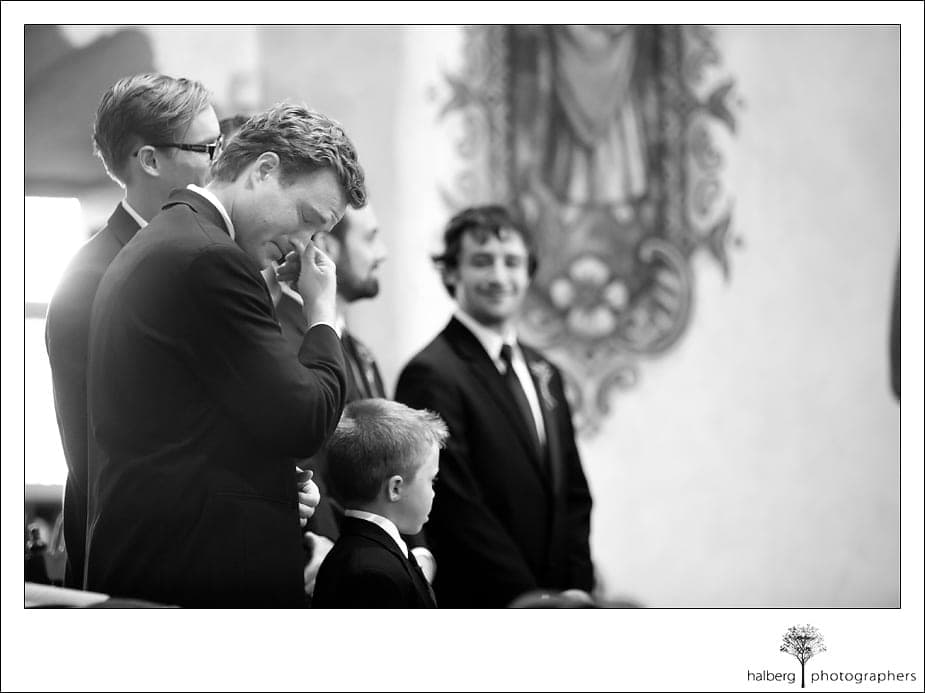 groom crying at alter while watching bride walk down isle
