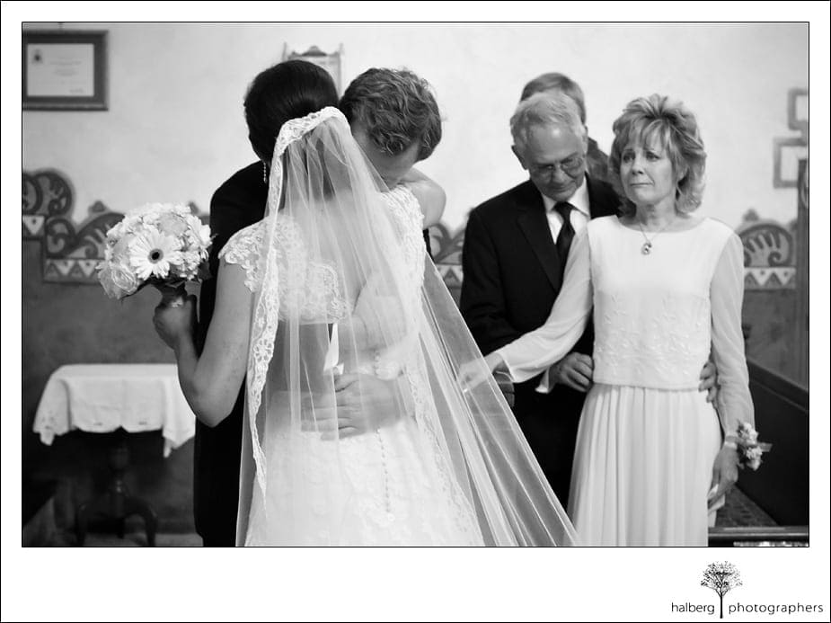 groom and bride hugging while parents look on at church