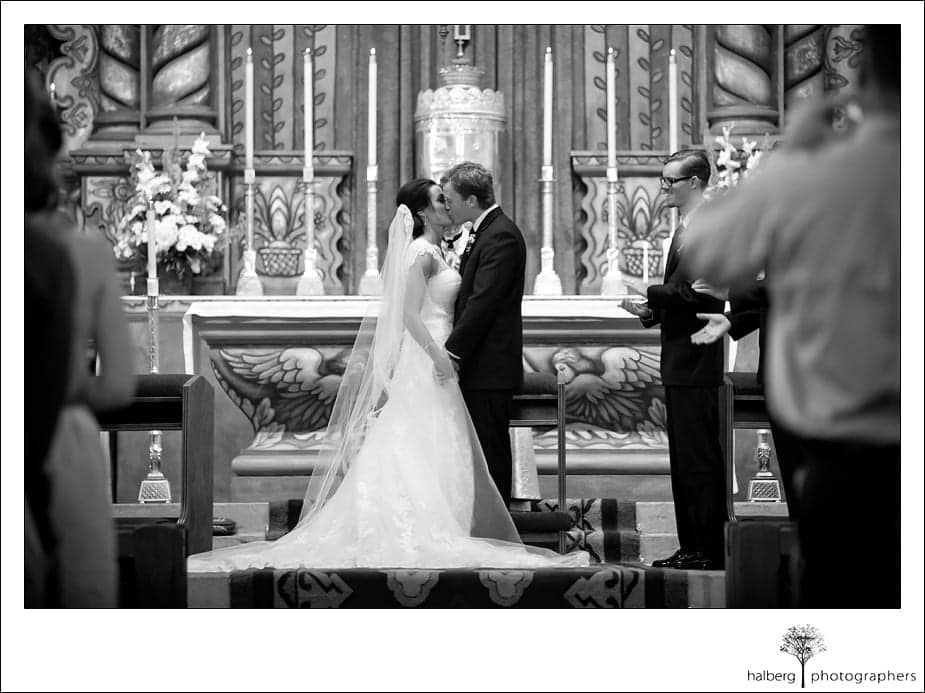 bride and groom kiss in church at their wedding ceremony