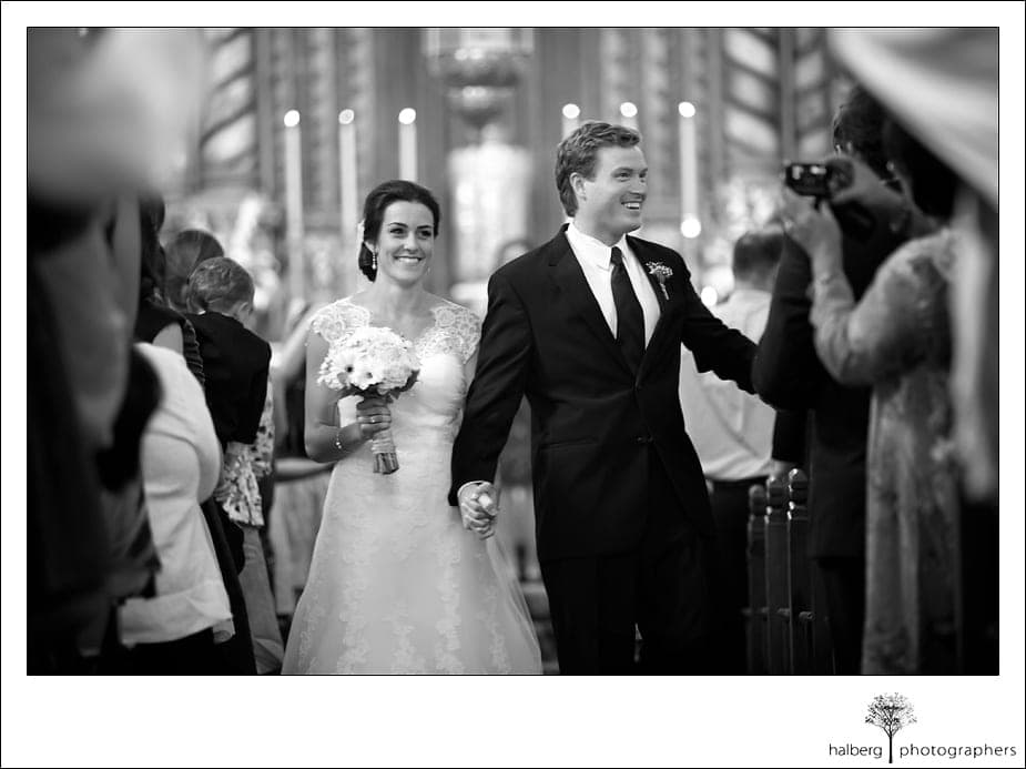 bride and groom walk down isle after wedding ceremony