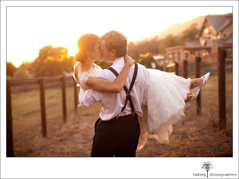 groom caries bride and kisses her at their Heartstone Ranch Wedding