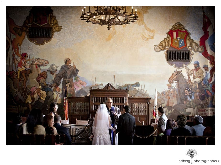 bride and groom at altar in mural room at their santa barbara courthouse wedding