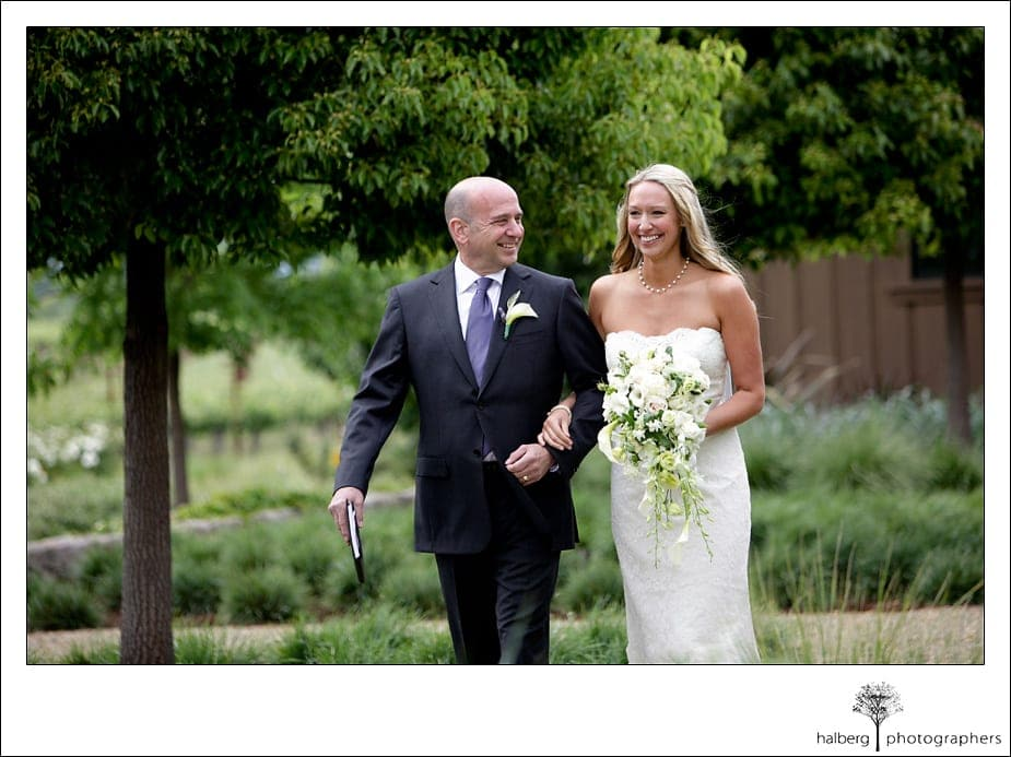 bride walks down isle with dad at her napa vineyard wedding