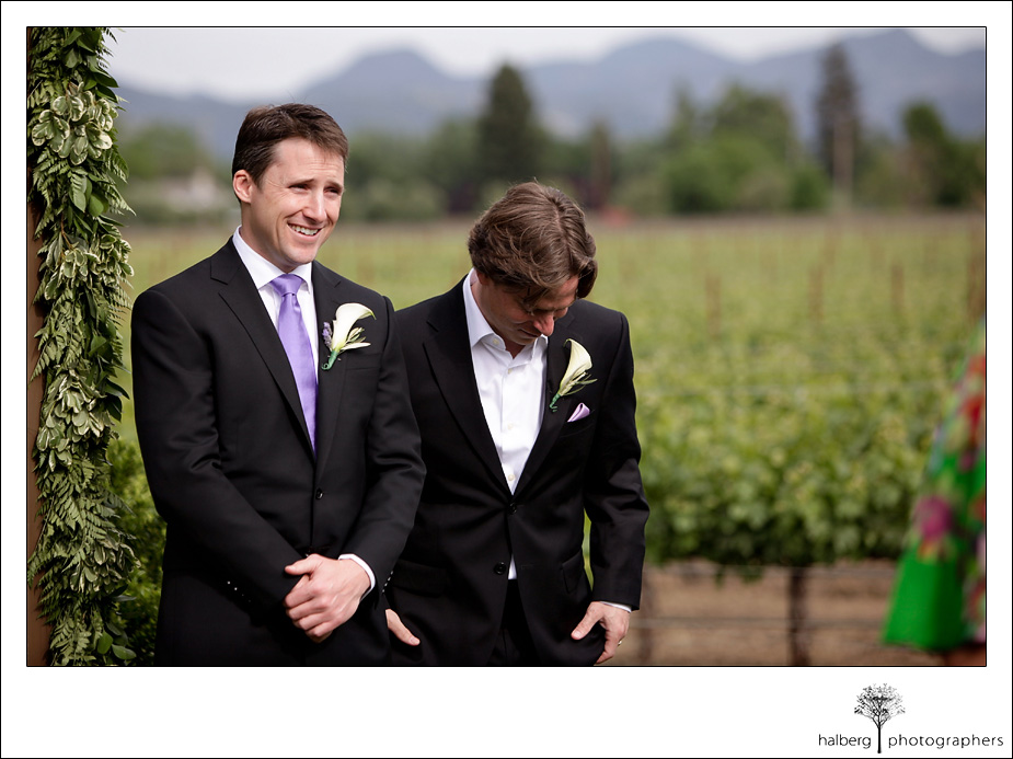 groom at alter as bride walks down isle of their napa vineyard wedding