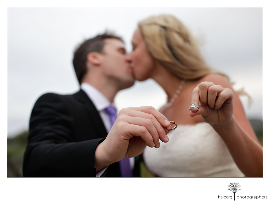 bride and groom holding rings out and kissing at their Napa Vineyard Wedding