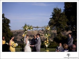 bride and groom holding hands at altar during their Firestone Vineyard Wedding