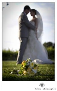 white and yellow bridal bouquet with wedding couple in background at Firestone Vineyard