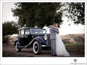 bride and groom kissing in front of old town car at their Firestone Vineyard Wedding