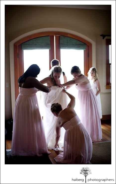 bride with bridesmaids putting her wedding dress on at Nicholson Ranch