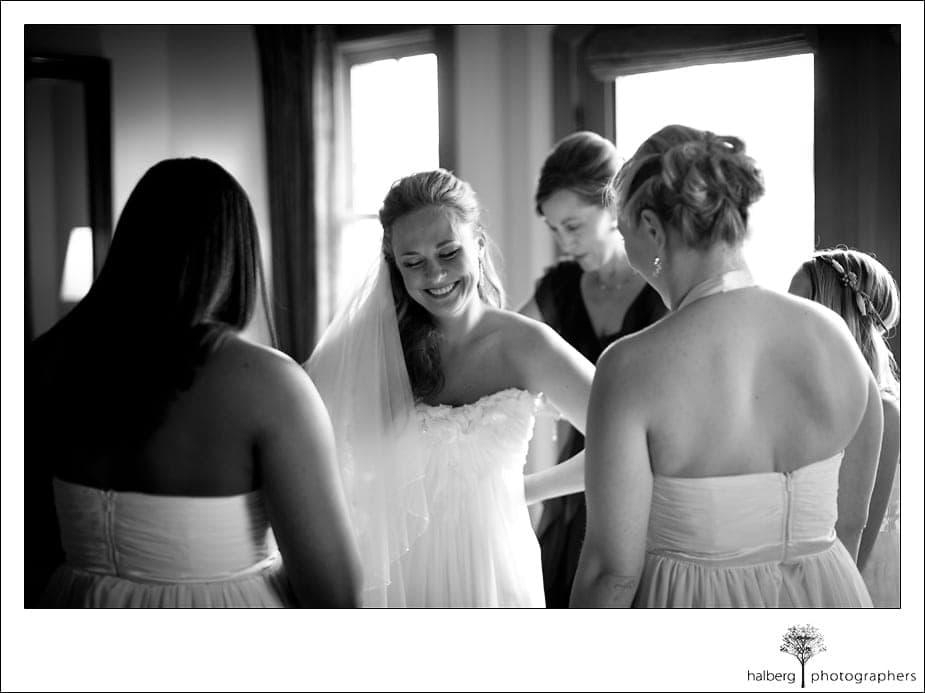 bride smiling while mom zips up her wedding dress at Nicholson Ranch