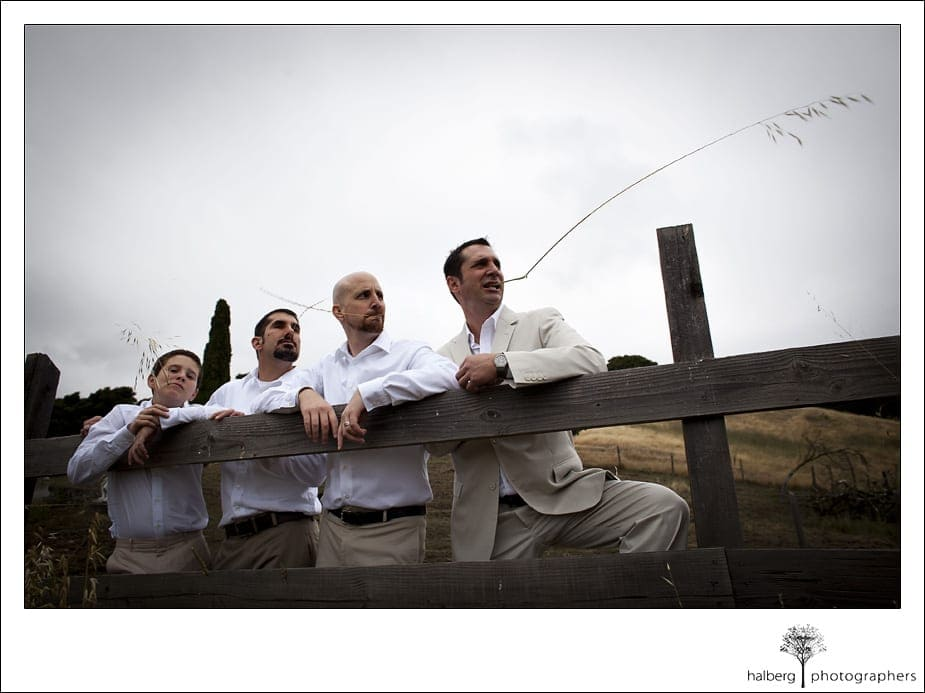 Nicholson Ranch Wedding groom and groomsmen pose behind wood fence