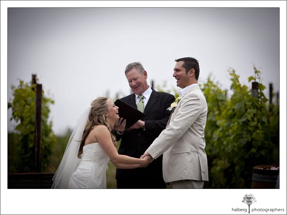 bride laughing holding grooms hand at alter for their Nicholson Ranch Wedding