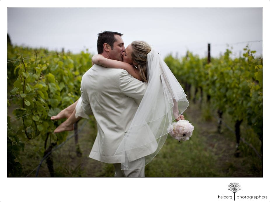 groom carrying bride through vineyards after their Nicholson Ranch Wedding