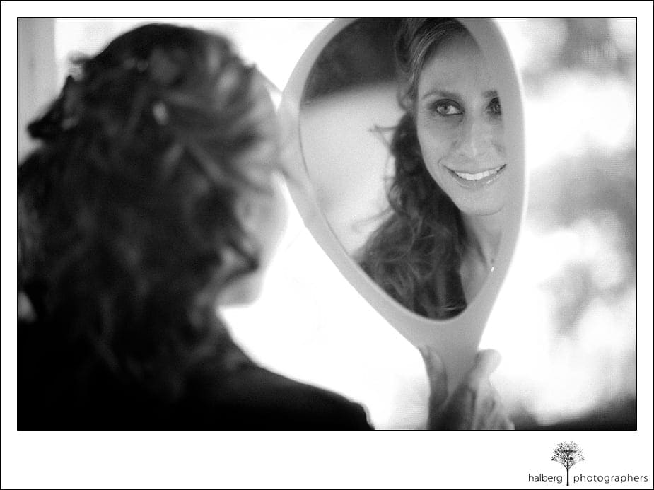 bride looking at herself in handheld mirror for her Riviera Country Club Wedding