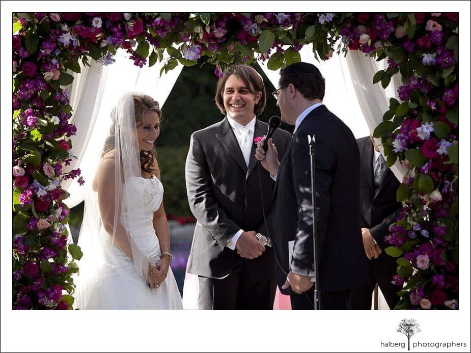 bride and groom laughing under chuppah at their Riviera Country Club Wedding
