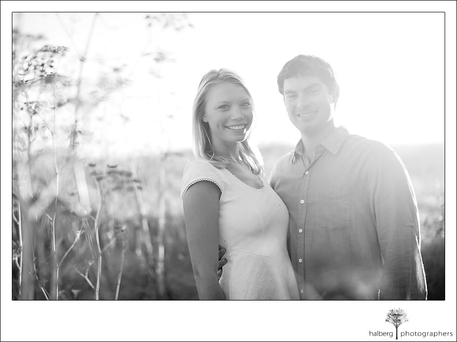 Engaged couple smiling in a field of tall grass in Santa Barbara