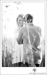 Groom kissing his bride's hand in a Santa Barbara field during their engagement session