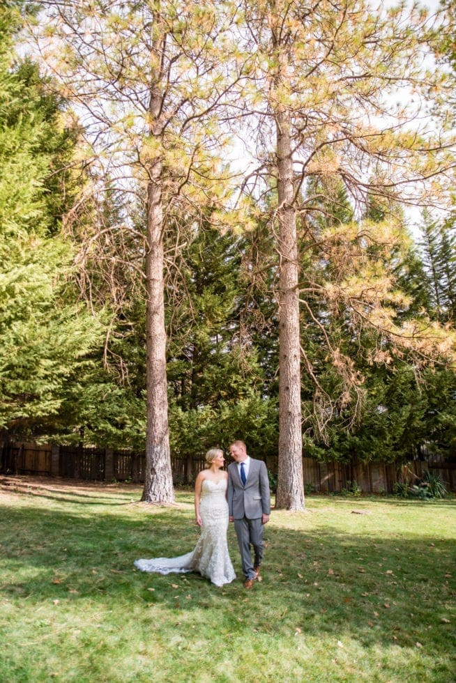 bride and groom looking at each other and walking toward the camera with trees in the background