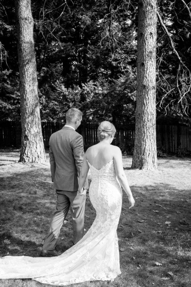 bride and groom holding hands and walking away from the camera with trees in the background